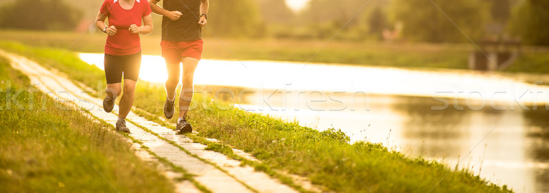 Couple running outdoors at sunset, by a river Stock photo © lightpoet