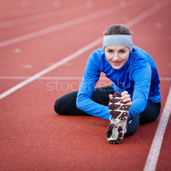 Stock photo: Young woman stretching before her run