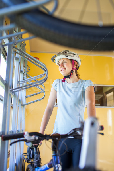 Cycling tourism: young woman traveling by train with her bike Stock photo © lightpoet