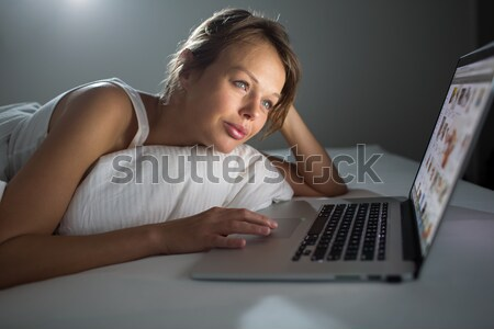 Pretty, young woman using her laptop computer in bed Stock photo © lightpoet
