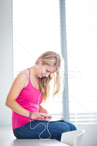 Pretty, young female student listening to music on her tablet Stock photo © lightpoet