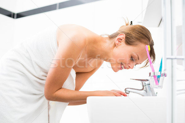 Pretty female brushing her teeth in front of mirror Stock photo © lightpoet