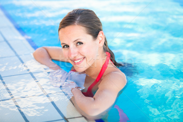 Stock photo: Portrait of a young woman relaxing in a swimming pool
