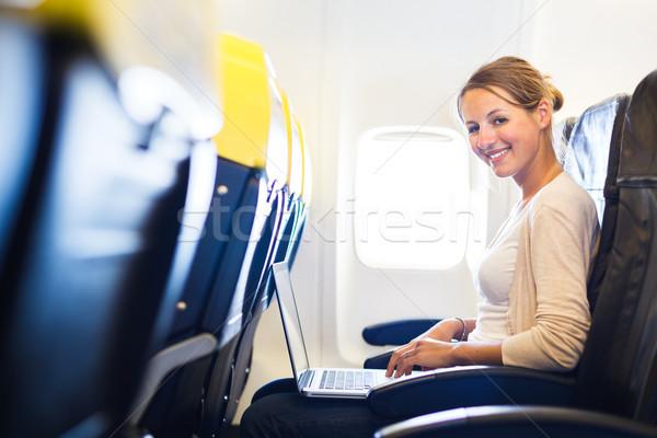 Fiatal nő dolgozik laptop számítógép tábla repülőgép számítógép Stock fotó © lightpoet