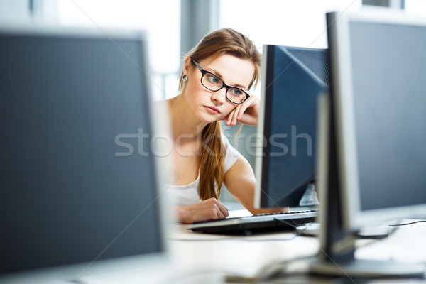 Pretty, female student looking at a desktop computer screen Stock photo © lightpoet