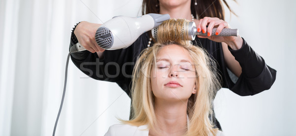 Pretty, young woman having her hair done by a l hairstylist Stock photo © lightpoet