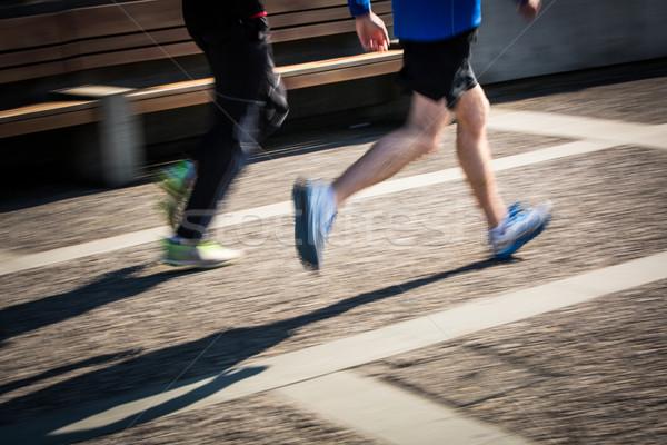 Motion blurred runner's feet in a city environment Stock photo © lightpoet