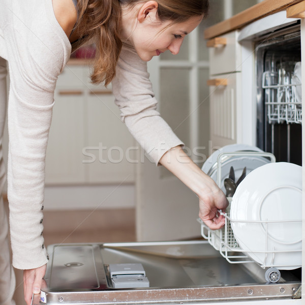 Stock photo: Housework: young woman putting dishes in the dishwasher