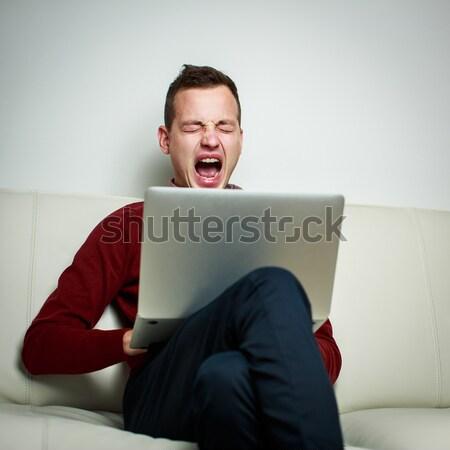 álmos fiatalember ül kanapé munka laptop számítógép Stock fotó © lightpoet