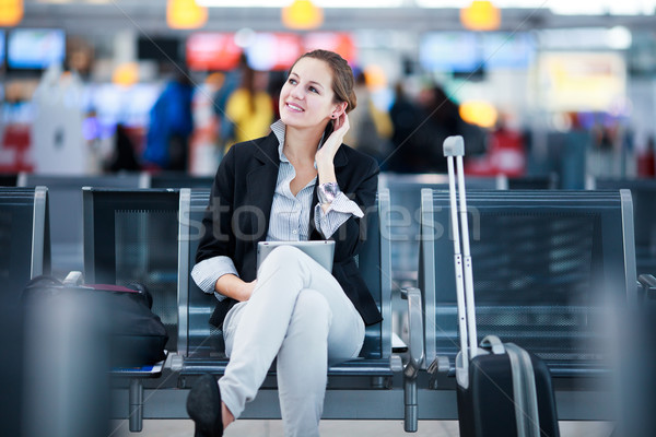 Stock photo: Young female passenger at the airport, using her tablet computer