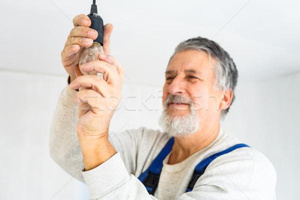 Senior man installing a bulb in a freshly renovated appartment Stock photo © lightpoet