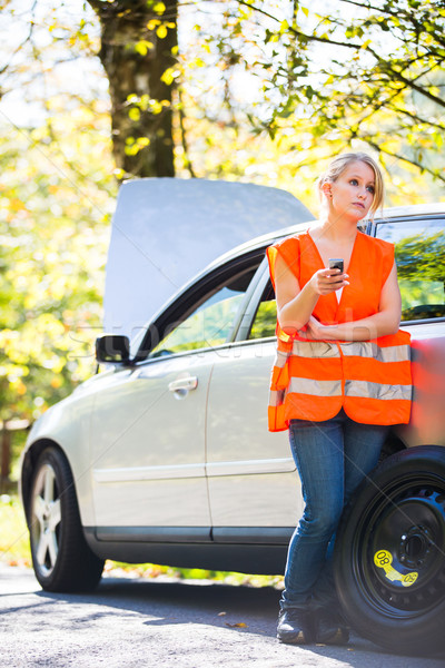 Young female driver wearing a high visibility vest, calling the  Stock photo © lightpoet