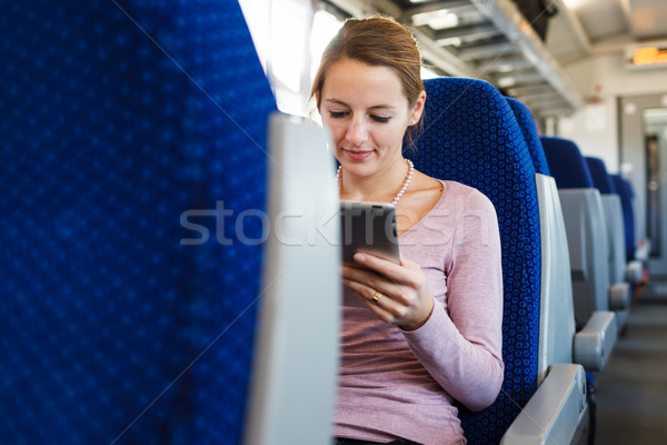 Young woman using her tablet computer while traveling by train Stock photo © lightpoet