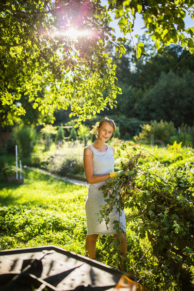 Pretty, young woman gardening in her garden, cutting branches Stock photo © lightpoet
