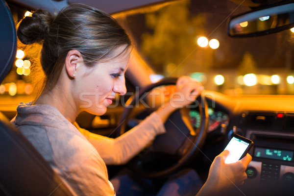 Pretty young woman using her smart phone while driving her car Stock photo © lightpoet