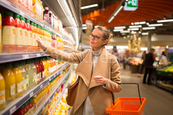 Pretty, young woman shopping for her favorite fruit juice/smooth Stock photo © lightpoet