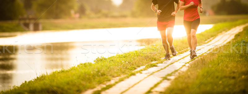 Couple running outdoors, at sunset, by a river, staying active Stock photo © lightpoet