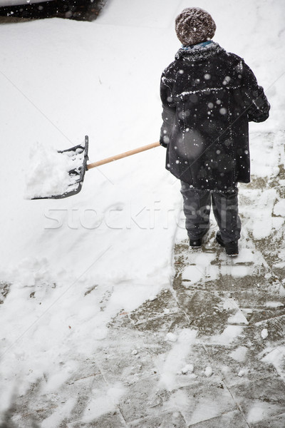 Man shoveling snow from the sidewalk in front of his house after Stock photo © lightpoet