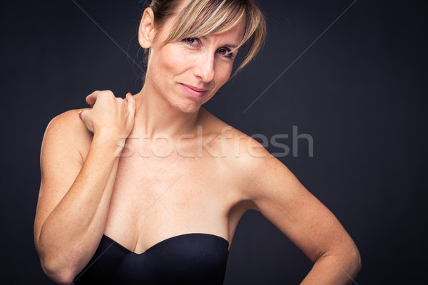 Portrait of a smiling middle aged caucasian woman against dark backgrount Stock photo © lightpoet