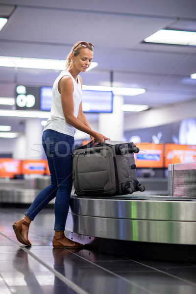 Man (traveler) picking up suitcase from baggage claim in airport Stock photo © lightpoet
