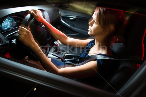 Driving a car at night - pretty, young woman driving her car Stock photo © lightpoet