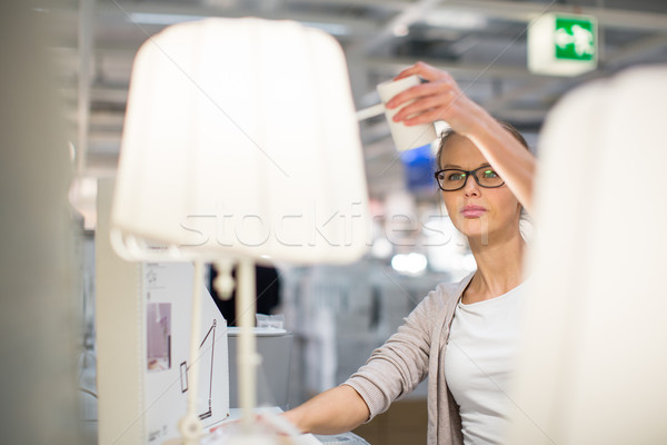 Pretty, young woman choosing the right light for her appartment  Stock photo © lightpoet