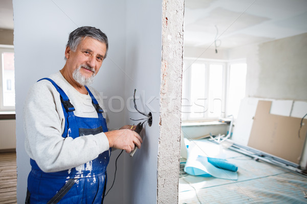 Senior man installing a bulb in a freshly renovated appartment Stock photo © lightpoet
