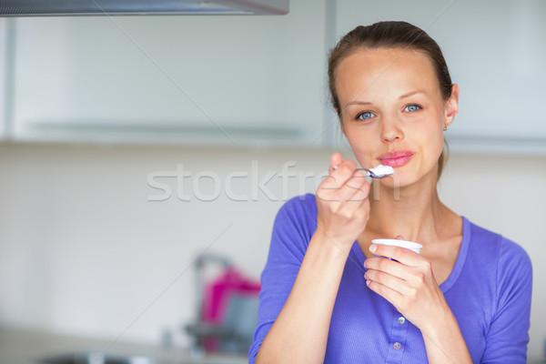 Happy young woman eating yogurt in kitchen Stock photo © lightpoet