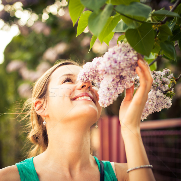 Beautiful young woman smelling white jasmin flowers Stock photo © lightpoet