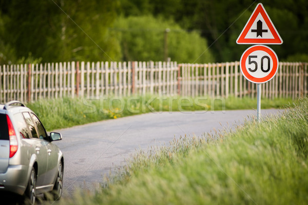 Car on a country road with limited speed and crossroad sign Stock photo © lightpoet