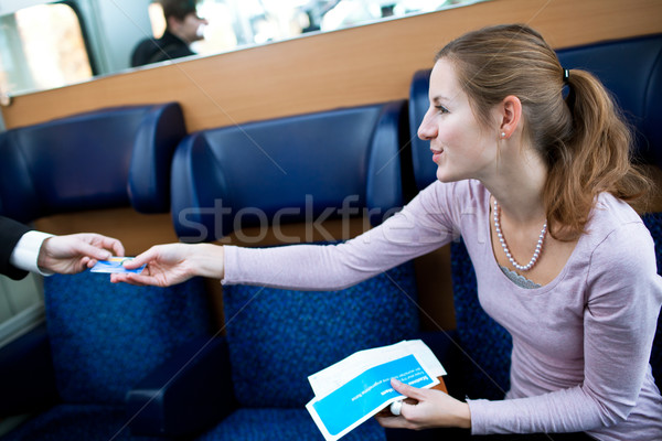 Young woman  having her ticket checked by the train conductor Stock photo © lightpoet