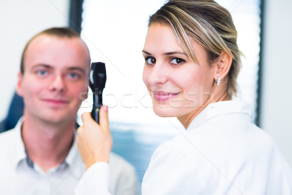 Handsome young man having his eyes examined by an eye doctor Stock photo © lightpoet