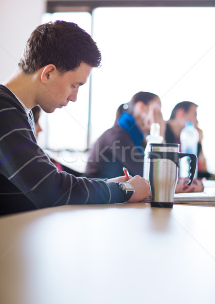 Stock photo: young, handsome male college student sitting in a classroom