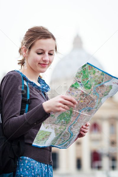Pretty young female tourist studying a map at St. Peter's square Stock photo © lightpoet