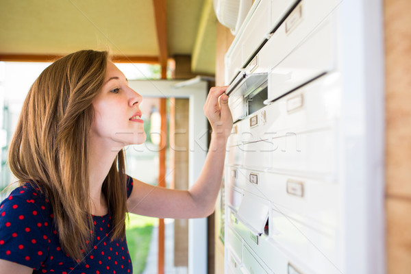 Pretty, young woman checking her mailbox for new letters Stock photo © lightpoet