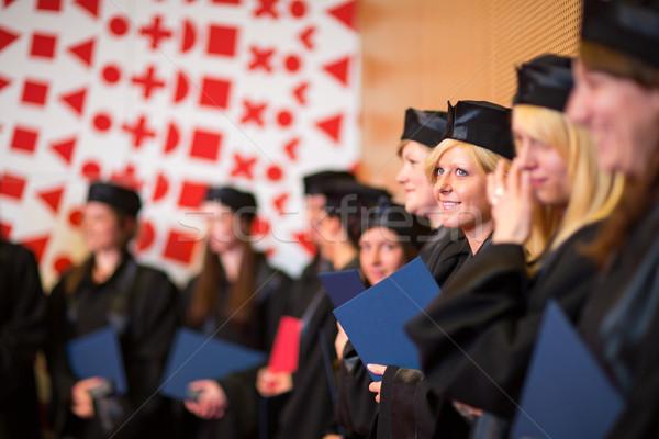 Pretty female college graduate at graduation with classmates Stock photo © lightpoet