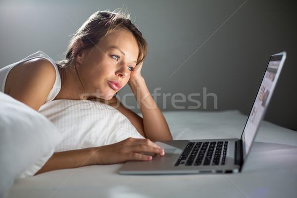 Csinos fiatal nő laptopot használ számítógép ágy szín Stock fotó © lightpoet