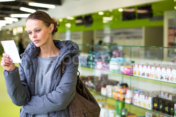 Young woman looking for the right pills in a modern pharmacy Stock photo © lightpoet