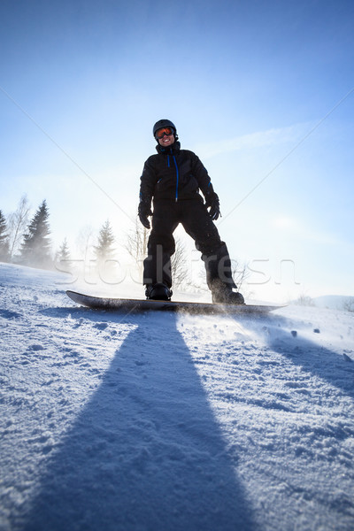 Young man snowboarding down a slope Stock photo © lightpoet