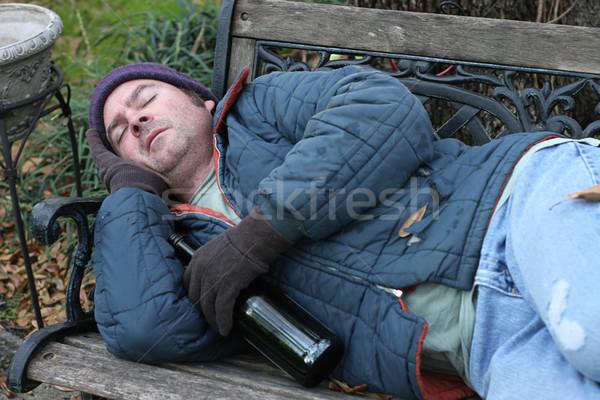 Hajléktalan férfi park pad alszik üveg Stock fotó © lisafx