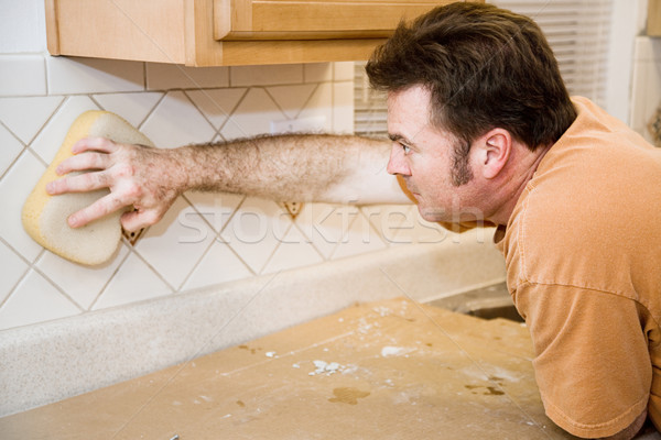 Tilesetter Wipes Down Tile Stock photo © lisafx