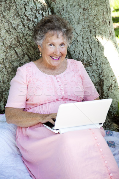 Kıdemli kadın netbook'lar açık havada ağaç yeni Stok fotoğraf © lisafx