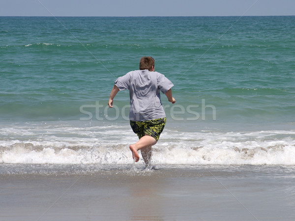 Buzgó úszás fiú tengerpart fut óceán Stock fotó © lisafx
