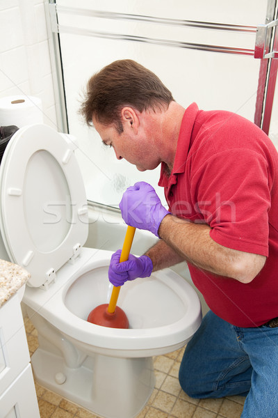 Man Using Plunger in Toilet Stock photo © lisafx