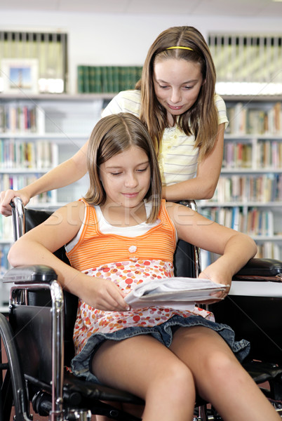 Two school girls reading notes in the library.