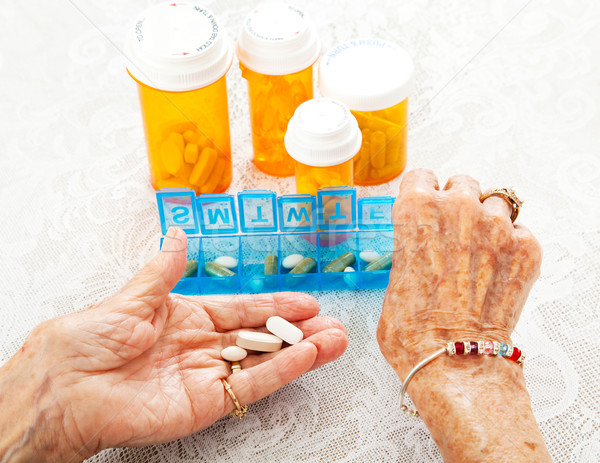 Idoso mãos pílulas ver oitenta Foto stock © lisafx