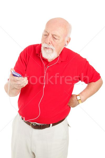 Senior man geërgerd mp3-speler muziek hoofdtelefoon Stockfoto © lisafx