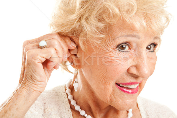 Stock photo: Senior Woman Inserts Hearing Aid