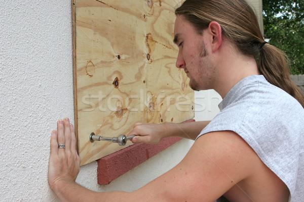 Sklejka okno młody człowiek domu przygotowanie huragan Zdjęcia stock © lisafx