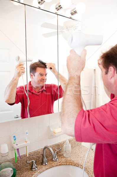 Man Blow Drying Hair in Bathroom Stock photo © lisafx
